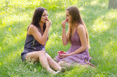 Two beautiful girls eating strawberries in sunny spring nature Stock Photos