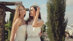 Two beautiful girls in elegant white dresses. Embroidered with stones in the crowns on their head posing in park on nature stock footage