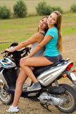 Two beautiful girls enjoying motorcycle ride at countryside Royalty Free Stock Photos