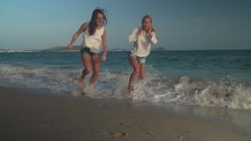 Two beautiful girls escape from the waves of South China Sea, Yalong Bay slow motion stock footage video stock video footage