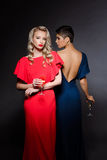 Two beautiful girls in evening dresses posing, holding champaign glass. Two beautiful blonde and brunette girls in red and blue evening dresses posing, looking Royalty Free Stock Photos