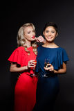 Two beautiful girls in evening dresses smiling, holding champaign glass. Stock Photography