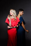 Two beautiful girls in evening dresses smiling, holding champaign glass. Two beautiful blonde and brunette girls in red and blue evening dresses smiling Royalty Free Stock Photo