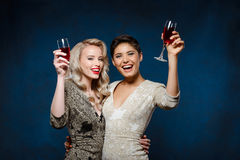 Two beautiful girls in evening dresses smiling, holding wine glasses. Two young beautiful blonde and brunette girls in evening dresses smiling, looking at stock photos