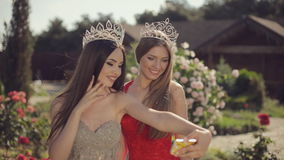 Two beautiful girls in evening gowns and crowns. Fooled around and doing selfie on phone in garden with roses stock video footage