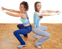 Two beautiful girls exercising together, smiling Royalty Free Stock Image
