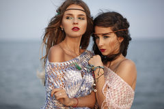 Two beautiful girls in fashion boho style at the sea. Two beautiful girls in fashion boho style Stock Images