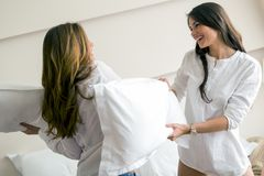 Two beautiful girls fighting with pillows. In a luxorious bedroom stock photos
