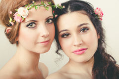 Two beautiful girls with flowers in head Royalty Free Stock Images