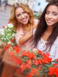 Two beautiful girls among flowers Stock Images