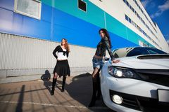 Two beautiful girls friend and white sports car Stock Photos