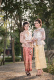 Two beautiful girls getting dressed in Thai Traditional Costume Royalty Free Stock Photos