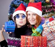 Two beautiful girls with gifts in christmas hats Stock Photo