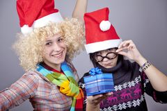 Two beautiful girls with gifts in christmas hats Stock Images
