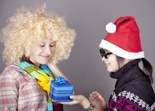 Two beautiful girls with gifts in christmas hats Royalty Free Stock Image