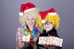 Two beautiful girls with gifts in christmas hats Royalty Free Stock Photo