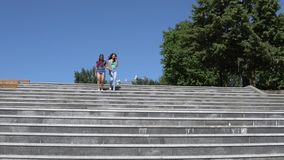 Two beautiful girls girlfriends are happy and jumping standing on the steps on the street. Two beautiful girls girlfriends are happy and jump standing on the stock video footage