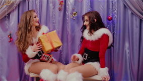 Two beautiful girls give gifts to one another. HD stock video