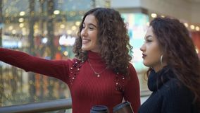Two beautiful girls with glasses of coffee are standing and chatting in the mall stock video footage