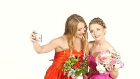 Two beautiful girls in gorgeous dresses taking. Two beautiful, pretty young girls in gorgeous red and pink  dresses taking selfie with flowers, on white stock video footage