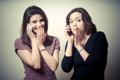 Two beautiful girls gossiping on the phone Royalty Free Stock Photos