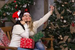 Two beautiful girls in hats Santa hats are shooting a selfie nea. Two beautiful girls in santa hats smiles make selfies near of Christmas tree. Two beautiful Royalty Free Stock Photos