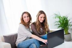 Two beautiful girls having fun at home Stock Photos