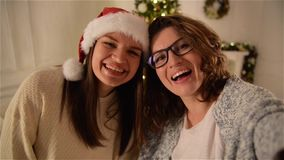 Two Beautiful Girls Having Fun Taking a Selfie on Christmas Tree Background. Brunette Sisters Using Smartphone and stock video