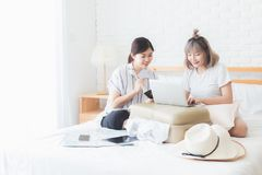 Two beautiful girls are helping each other plan to book accommodation and plane tickets on notebook computers, travel packages. Two beautiful girls are helping royalty free stock photo