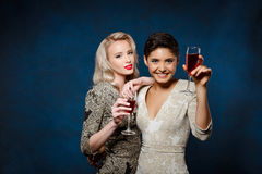 Two Beautiful Girls In Evening Dresses Smiling, Holding Wine Glasses. Royalty Free Stock Images