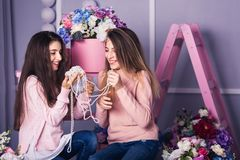 Two beautiful girls in jeans and pink sweaters are holding beads in studio with decor of flowers in baskets. Royalty Free Stock Photos