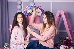 Two beautiful girls in jeans and pink sweaters are holding beads in studio with decor of flowers in baskets. Stock Images