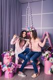 Two beautiful girls in jeans and pink sweaters are holding beads in studio with decor of flowers in baskets. Royalty Free Stock Photo