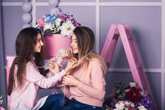 Two beautiful girls in jeans and pink sweaters are holding beads in studio with decor of flowers in baskets. Royalty Free Stock Photography