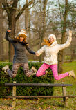 Two beautiful girls jumping from the bench Royalty Free Stock Photos