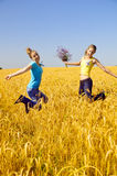 Two beautiful girls jumps in golden field Stock Photography