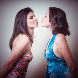 Two beautiful girls kissing. On gray background Stock Image
