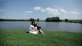 Two beautiful girls with lambs. girls on the  river. Two beautiful girls with lambs. girls on the bank of a picturesque river. girls rest on the shore of a stock video footage