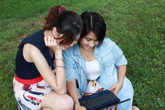 Two beautiful  girls with laptop. Two beautiful girl with a laptop computer outdoors. Lay on the green grass Royalty Free Stock Image