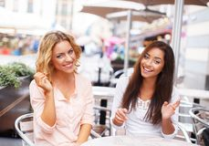 Two beautiful girls with laptop. Two beautiful girls chatting in summer cafe Stock Photography