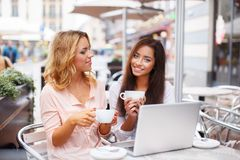 Two beautiful girls with laptop. Two beautiful girls cups and laptop in summer cafe Stock Images