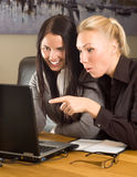 Two beautiful girls with laptop in the office Royalty Free Stock Photo