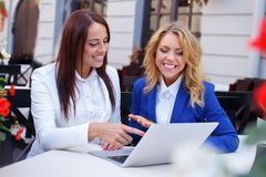 Two beautiful girls with laptop. In summer cafe Stock Images