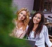 Two beautiful girls with laptop. In summer cafe Royalty Free Stock Photography