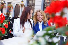 Two beautiful girls with laptop. In summer cafe Royalty Free Stock Photos