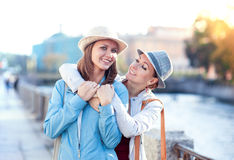Two beautiful girls laughing and hug in the city Stock Photos