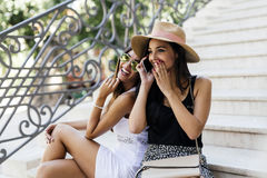 Two beautiful girls laughing while talking on phone. With a boy Royalty Free Stock Photo