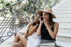 Two beautiful girls laughing while talking on phone. With a boy Stock Photos