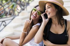 Two beautiful girls laughing while talking on phone. With a boy Stock Photo