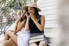 Two beautiful girls laughing while talking on phone. With a boy Stock Photography